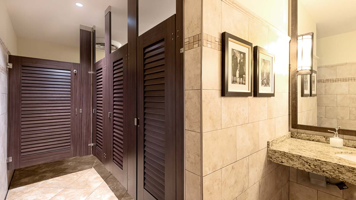 Neutral tone tile bathroom features ceiling hung, dark wood grain compact laminate bathroom partitions with louver doors. Black and white pictures.