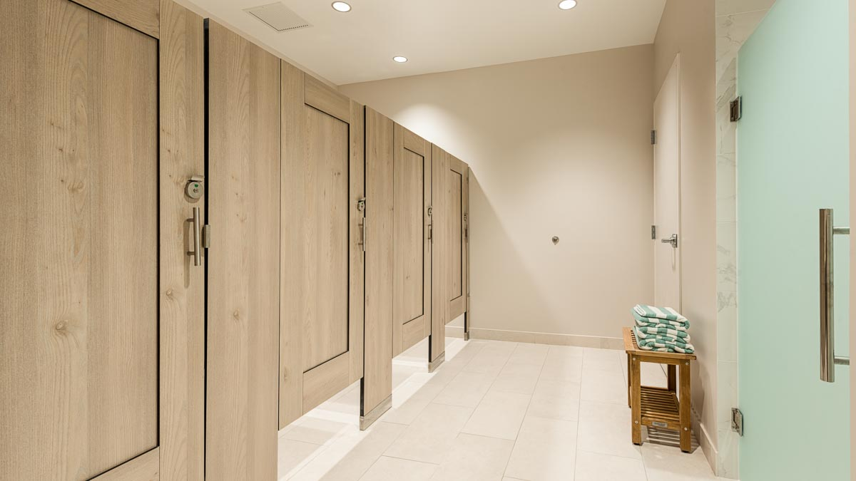Country Club bathroom shows compact laminate dressing compartments with light tan, wood grain captured panel doors opposite frosted green shower door.