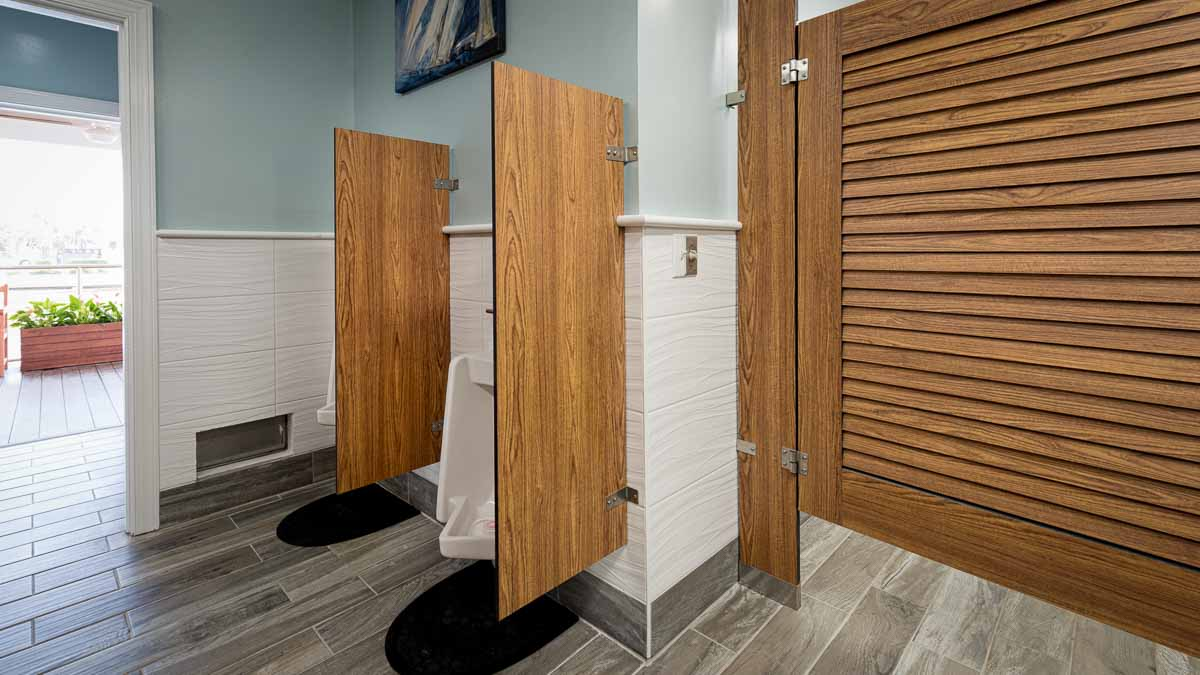 Classy marina bathroom featuring compact laminate, wood grain louver door with sailboat print over two urinal privacy screens. Pier outside open door.