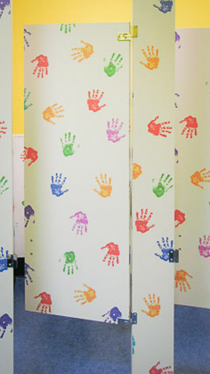 Day care center bathroom featuring white custom laminate with colorful, playful handprints on child size door and pilaster.