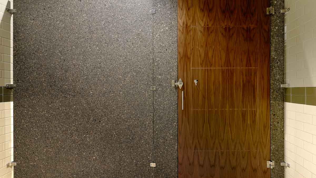 Business showroom bathroom featuring one grey speckled engineered stone panel and pilasters with engraved rectangular pattern, wood veneer door.