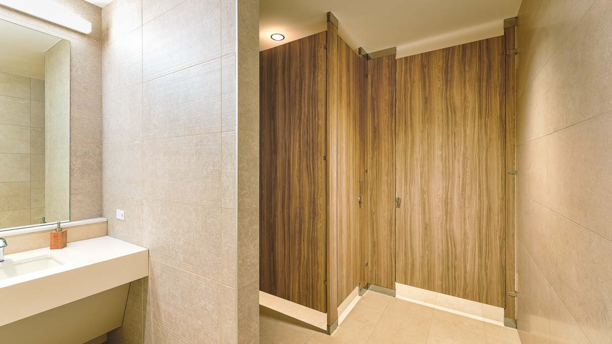 All gender, upscale business office bathroom features high privacy zero sightline partitions and handsome, wood grain laminate doors. Tan tiled room.