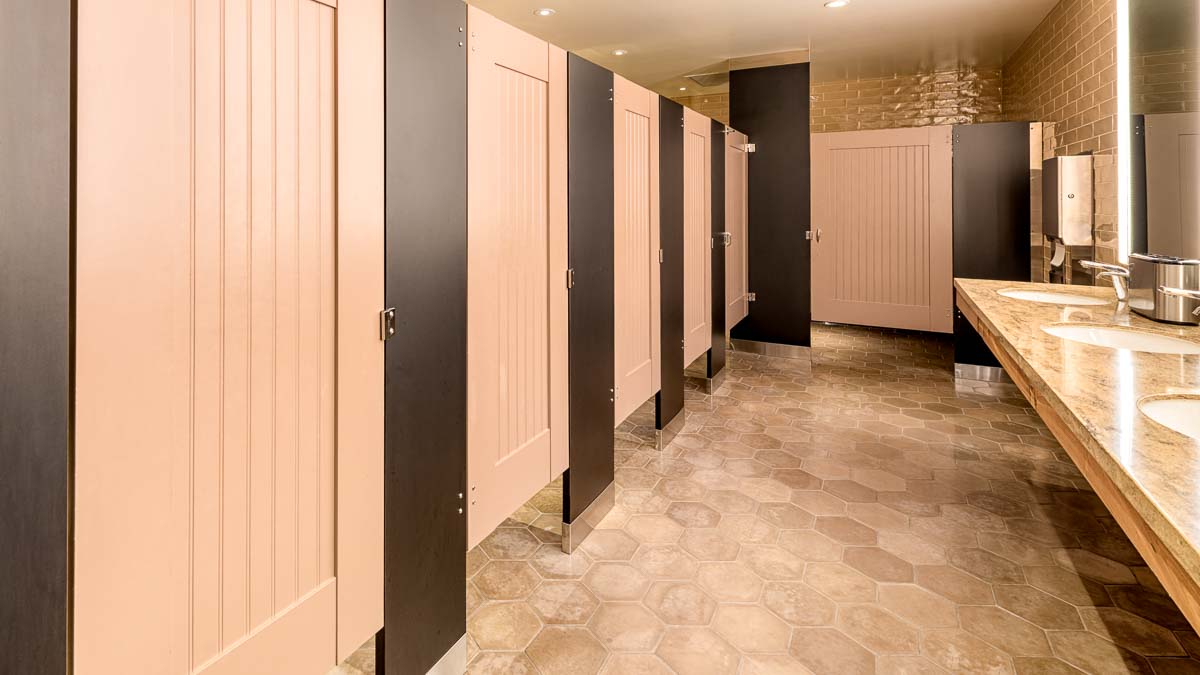 Large subway tile hotel bathroom featuring six tan painted laminate partitions with captured panel with bead board insert and dark brown pilasters.