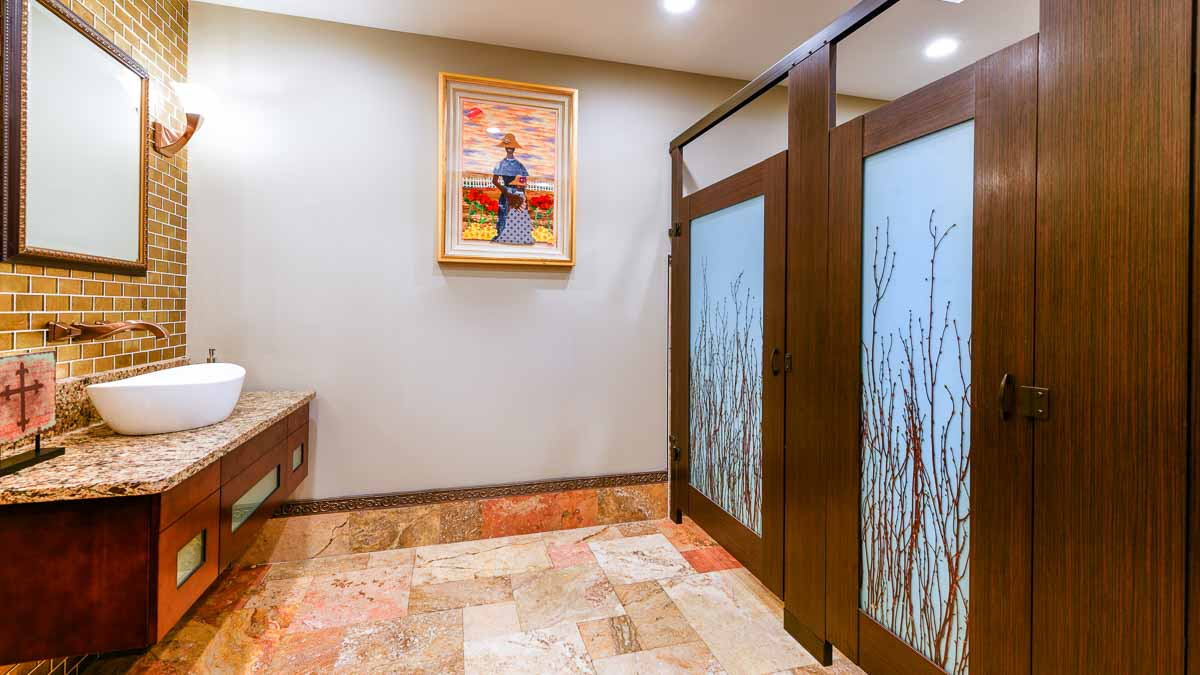 Radiant church restroom features brown laminate partitions with birch branch design on two translucent acrylic doors. Bronzed fixtures and cross.