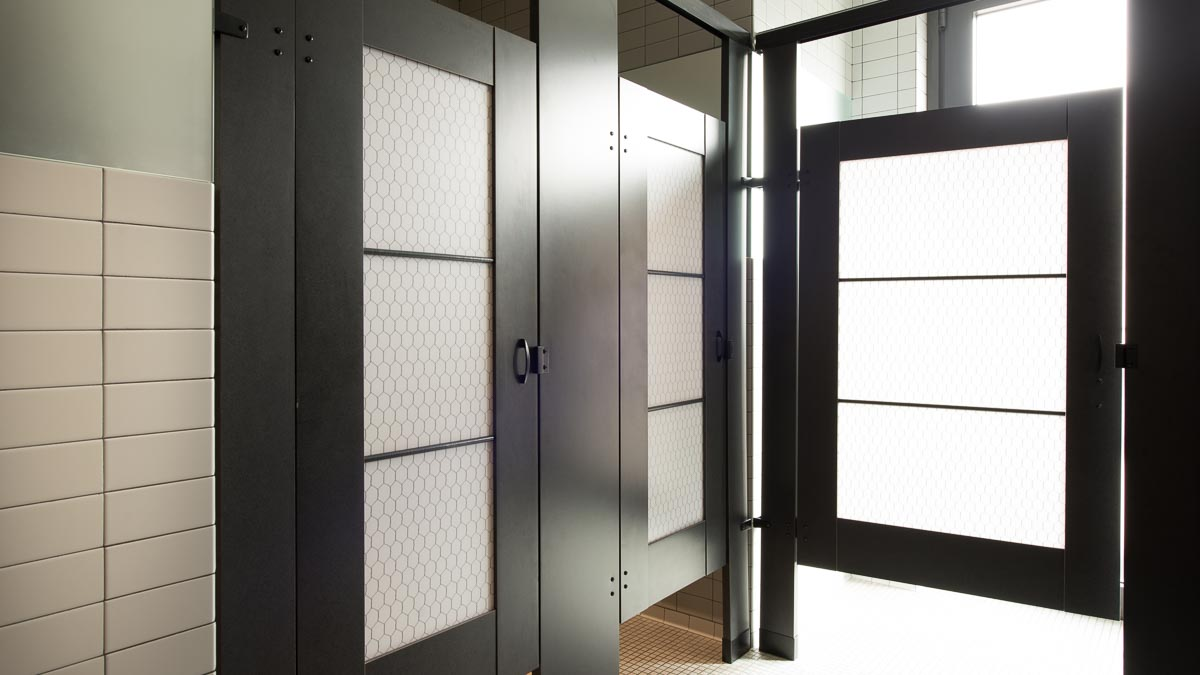 Unique hotel bathroom with standard size, black laminate partitions showcasing chicken wire design on acrylic door lite inserts.