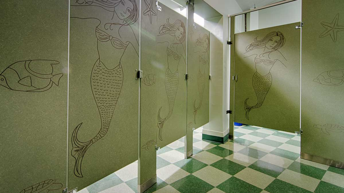Green and white tiled floor bathroom showcases mermaids and sea life engravings on four light green laminate partitions.