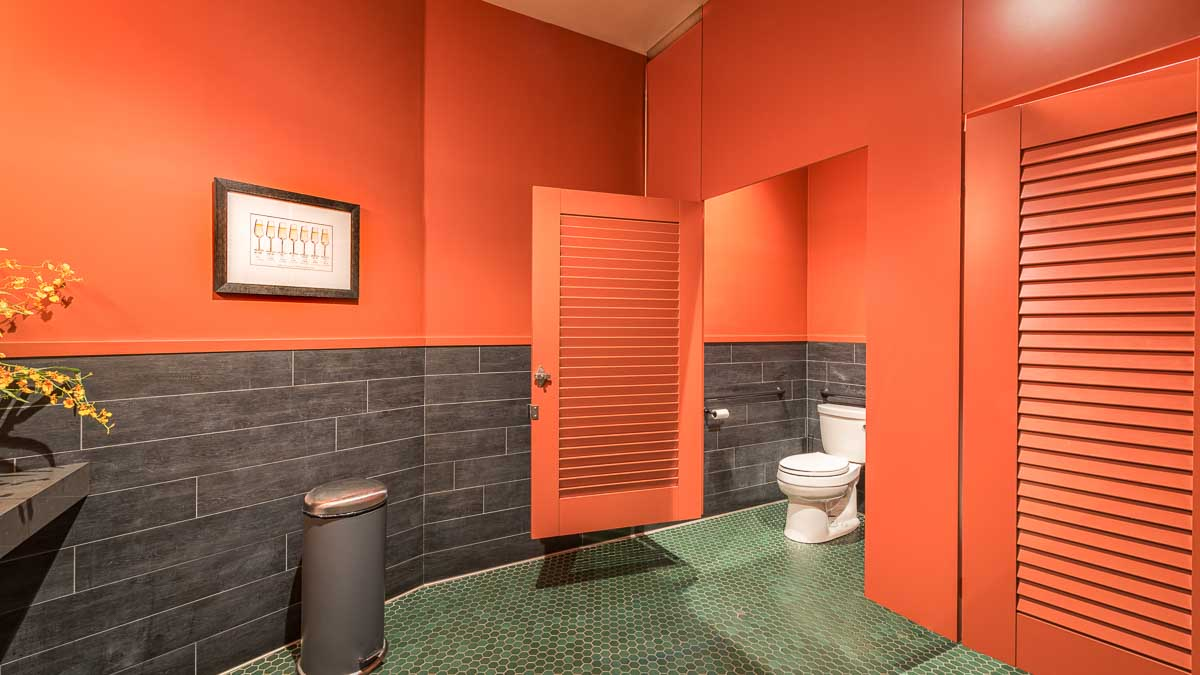 Winery bathroom painted bright orange in ceiling hung style with two louver doors and transom. Green tile floor and wine glass print on wall.