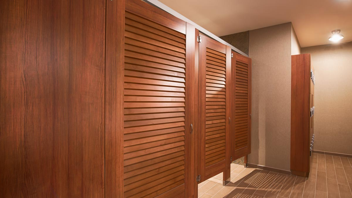 Country Club bathroom featuring plastic laminate partitions with three, medium brown louver doors. Matching combination lockers at end of room.