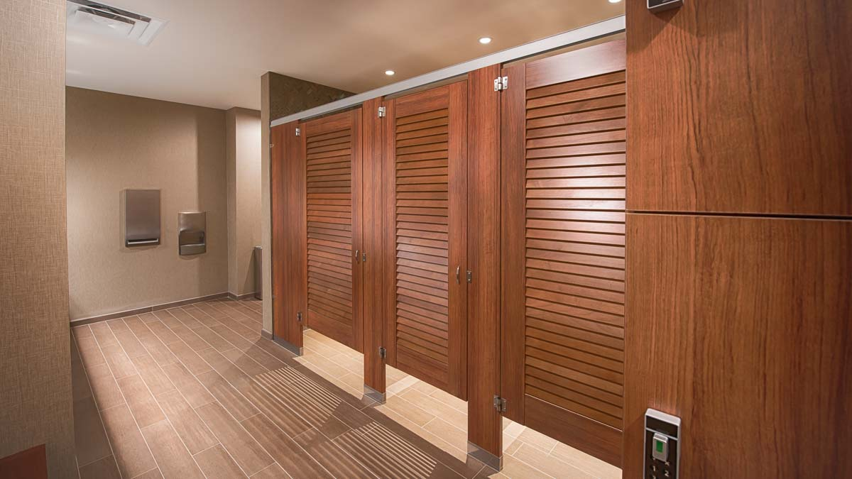Hotel locker room features three, plastic laminate dressing compartments and lockers in. Brown tan tiled floor with tan linen look wall covering.