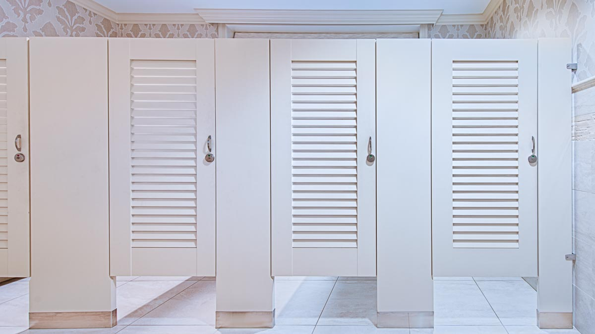 Country club bathroom highlighting zero sightline laminate toilet partitions with louver doors resulting in a clean, seamless appearance.