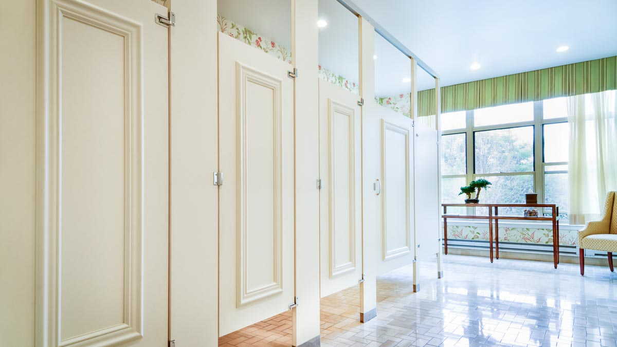 Elegant bright bathroom featuring white laminate partitions and doors accented with picture frame molding stained to match laminate.