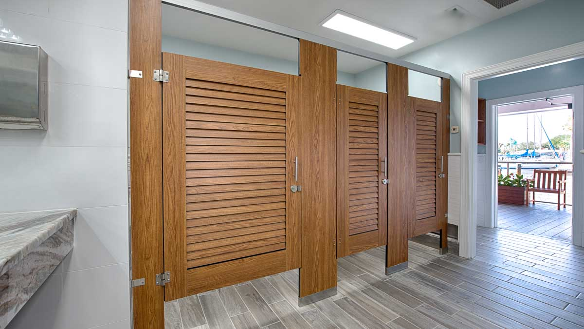 Marina bathroom featuring compact laminate, dark wood grain louver doors in headrail braced style. Open door shows pier with sailboat in background.