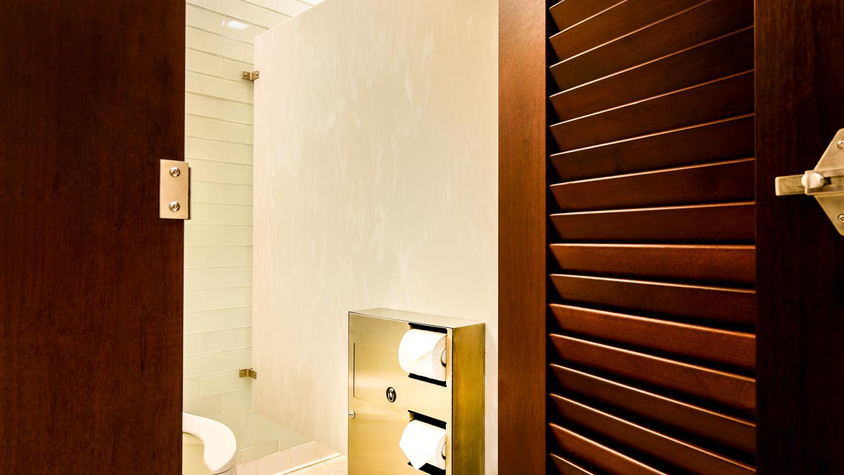 Open dark brown, wood veneer louver door showing inside of stall with tan and white solid surface panel with gold finish toilet paper dispenser.