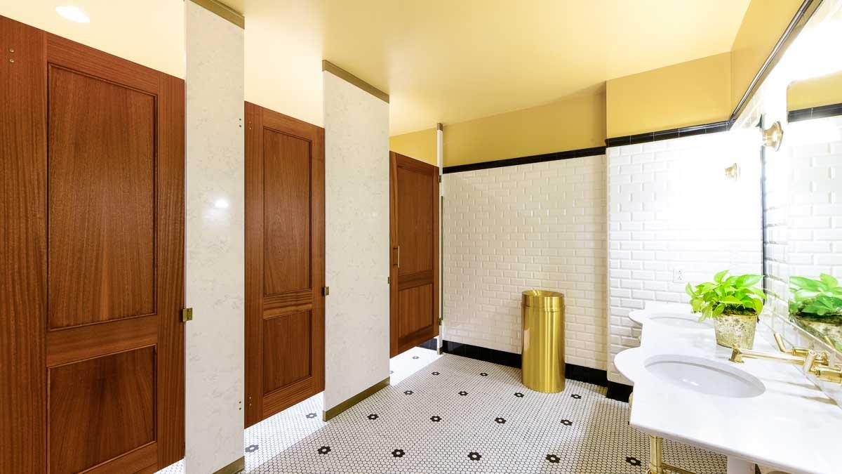 Posh business headquarters tiled bathroom features engineered stone pilasters with three wood veneer, captured panel doors in floor to ceiling style.