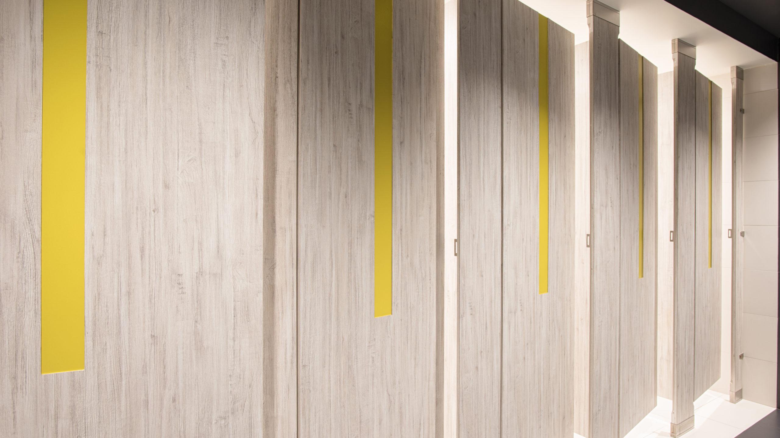 "Five grey variegated, zero sightline, laminate bathroom doors feature bright yellow 4"" door lite insert bringing a stylish modern look."