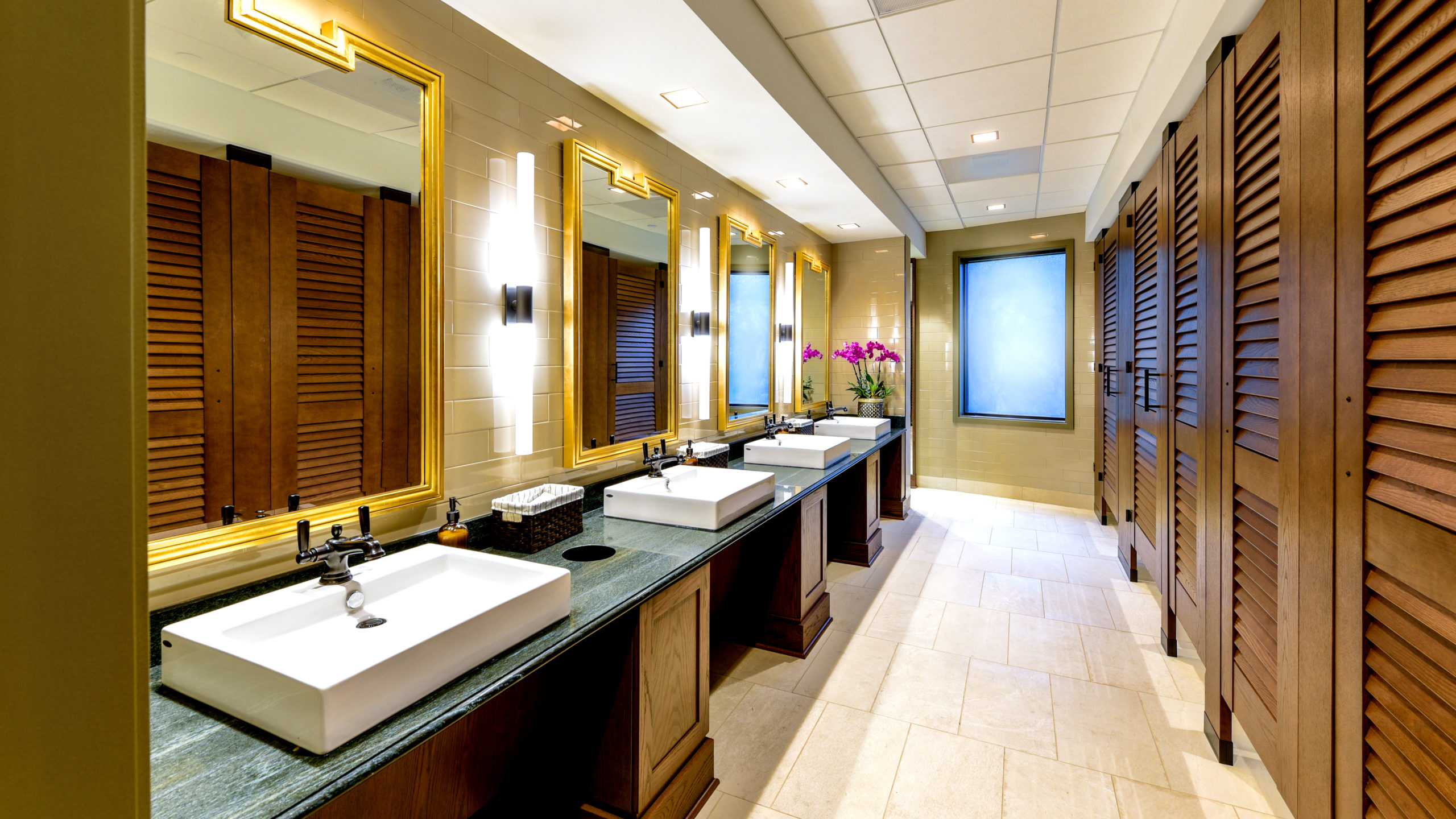 Upscale bathroom showing five, high privacy wood grain laminate partitions with louver doors opposite green marble vanity with white raised sinks.