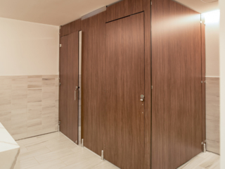 Executive office employee bathroom in compact laminate partitions with full height configuration showing transoms for added privacy.