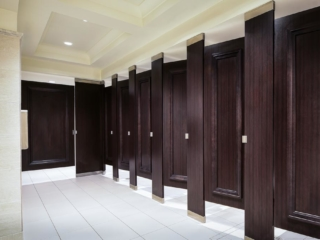Seven full height dark wood grain laminate bathroom partitions and doors accented with picture frame molding stained to match laminate.