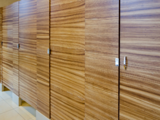 Seattle hotel bathroom with four wood veneer (zebrawood) floor mount partitions highlight a rich wood grain presentation.