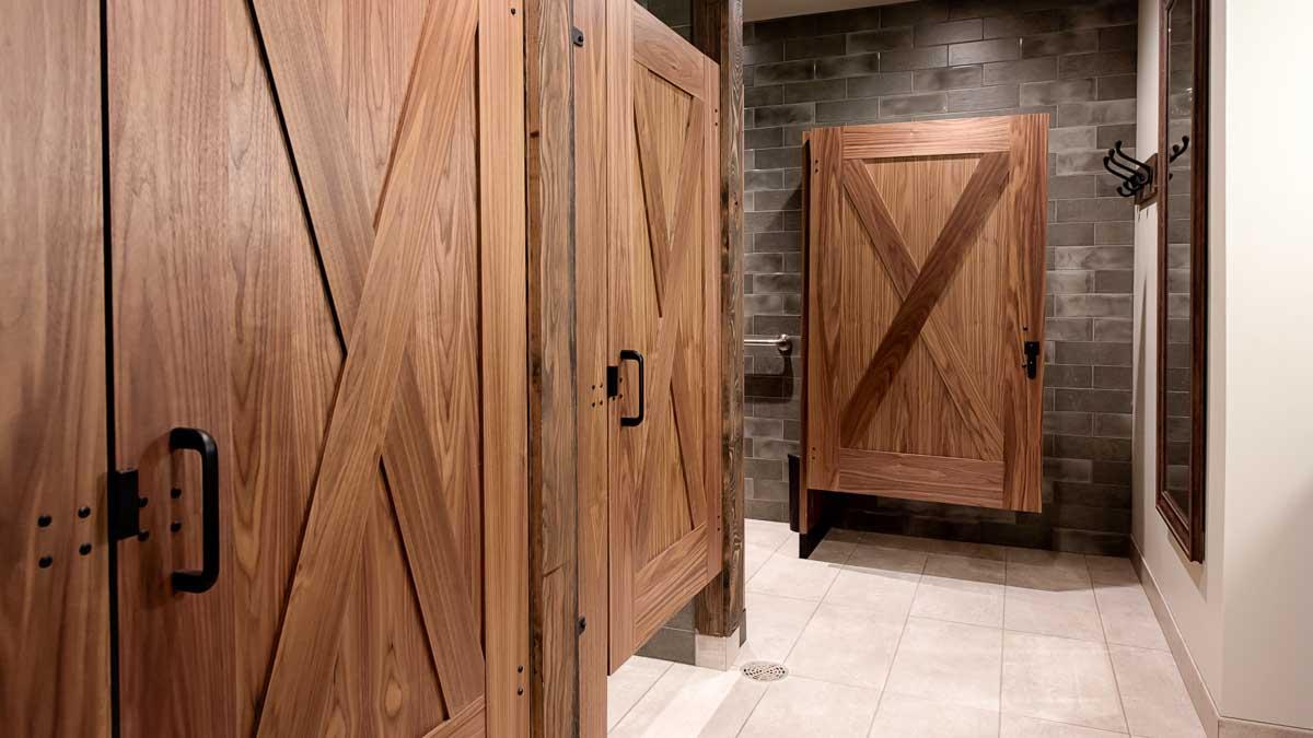 Luxury Montana lodge bathroom features three wood veneer captured panel doors with large X shape on both sides of doors in grey subway tiled room.