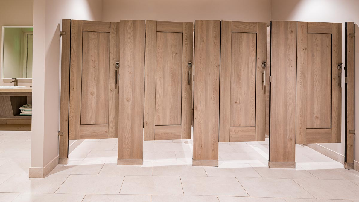 Country Club bathroom featuring floor mount, compact laminate partitions with light tan, wood grain captured panel with slightly opened doors.