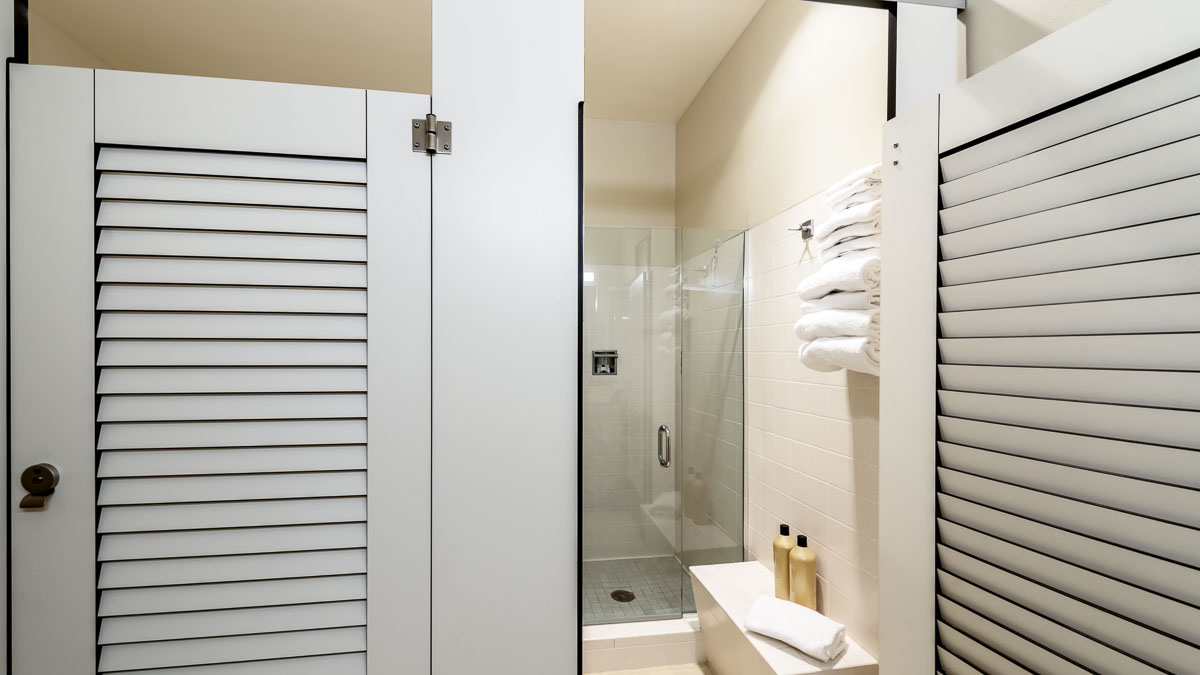 Two pretty, white compact laminate dressing compartments with louver doors. Open door shows changing area with products on bench and rolled towels.
