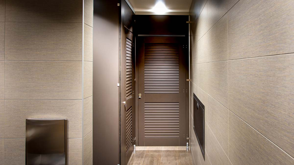 Clean look at dealership showroom bathroom shows high privacy toilet partitions in full height, dark brown louver doors with transoms.