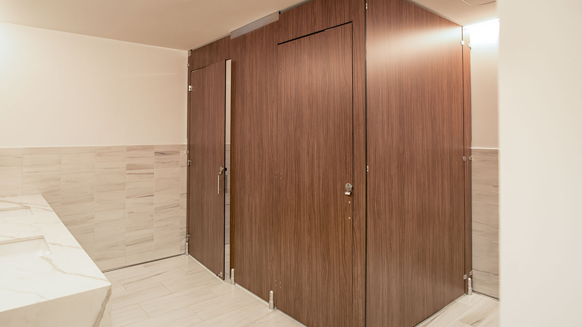 Executive office employee bathroom in compact laminate partitions with oversize configuration showing transoms for added privacy.
