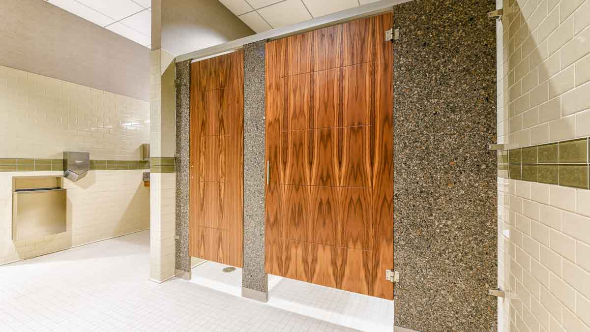 White subway tiled business showroom bathroom featuring two gorgeous wood grain, engraved veneer doors with grey speckled engineered stone pilasters.