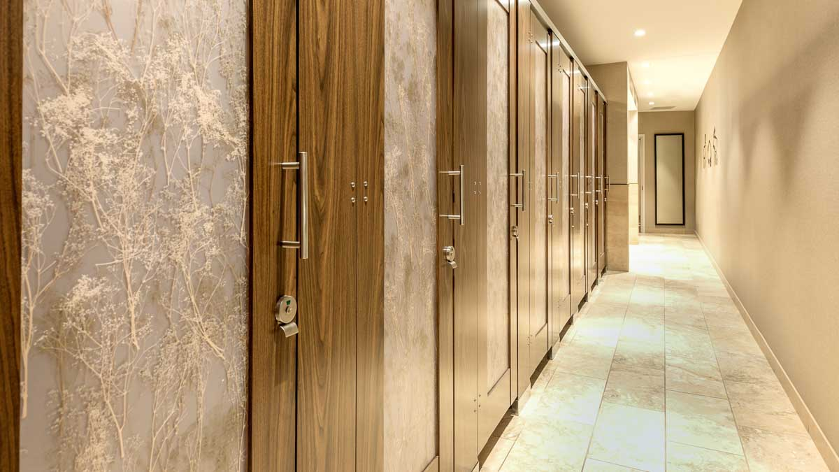 Expansive wildlife museum bathroom features eight laminate doors with natural organic baby's breath design on translucent acrylic door lite inserts.