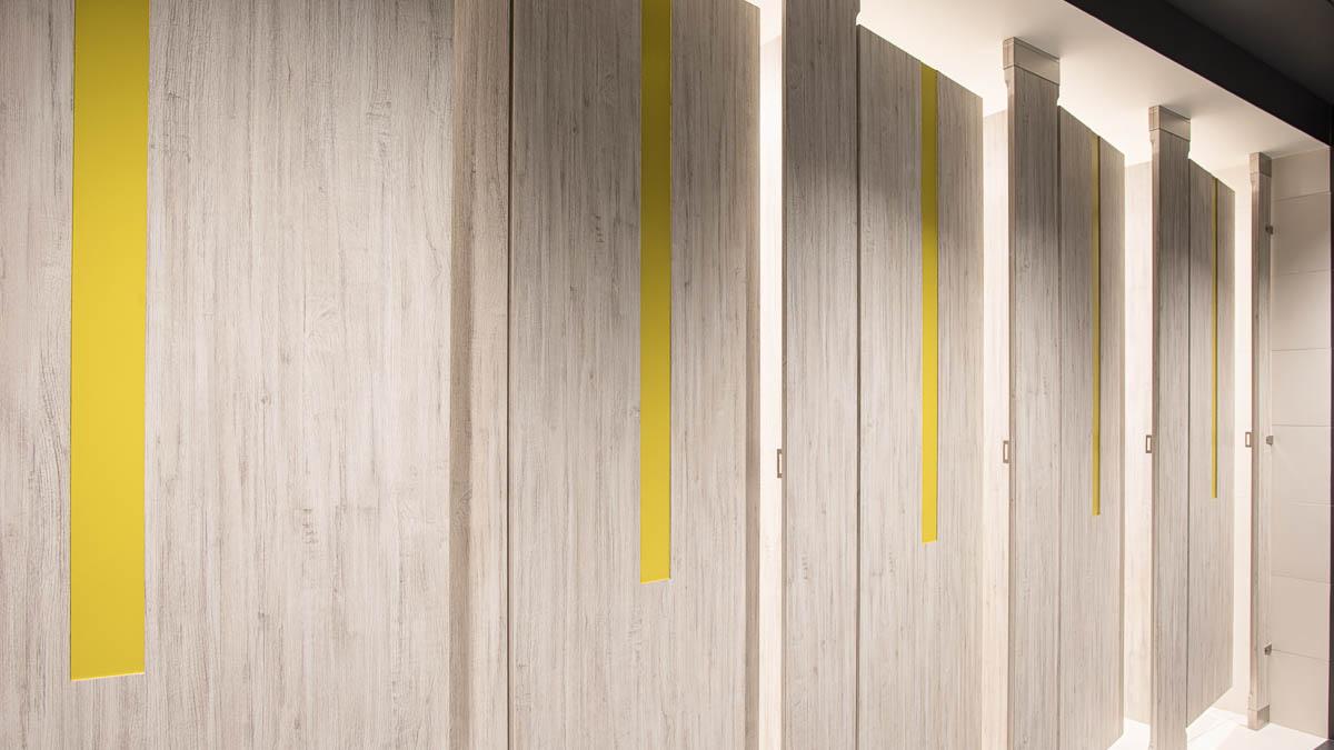 "Five grey variegated, laminate bathroom doors feature bright yellow 4"" door lite insert creating modern, fresh appearance."