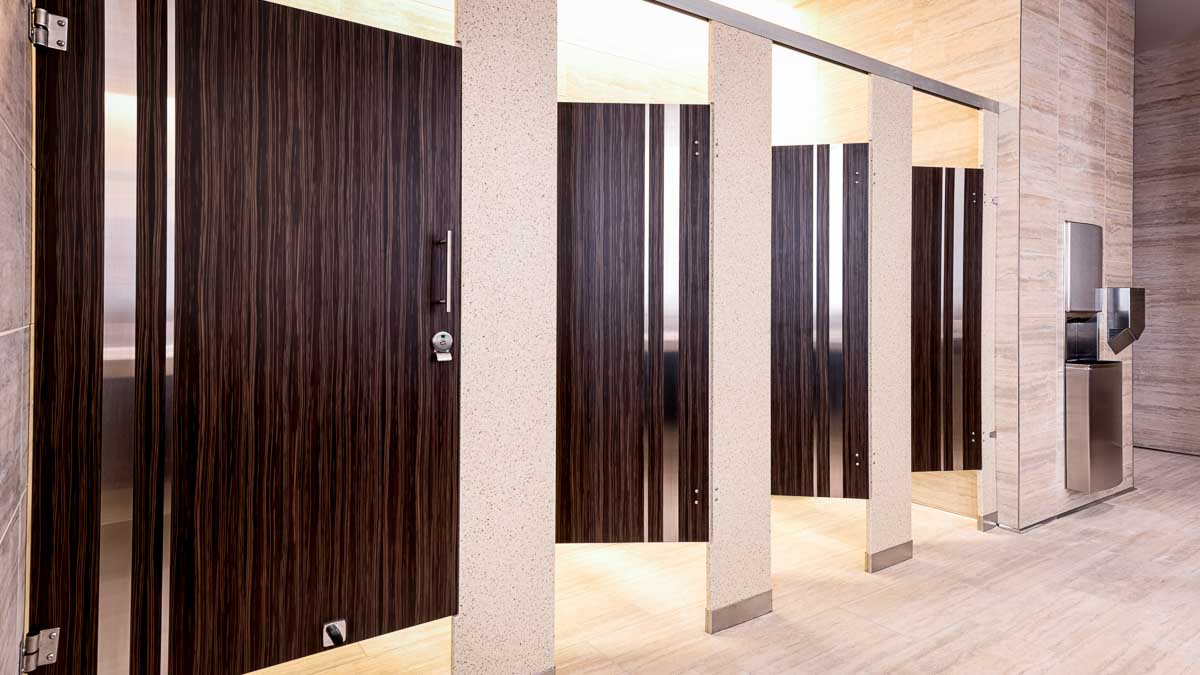 Upscale casino bathroom with solid surface pilasters and four plastic laminate wood grain opened doors with vertical stainless steel insert strips.