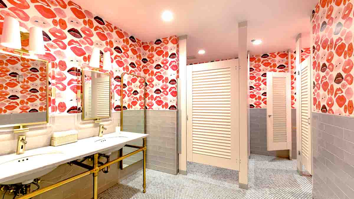 Wallpaper full of large red lips and cream subway tiles on wall showcase bright white laminate louver bathroom doors in floor to ceiling style.
