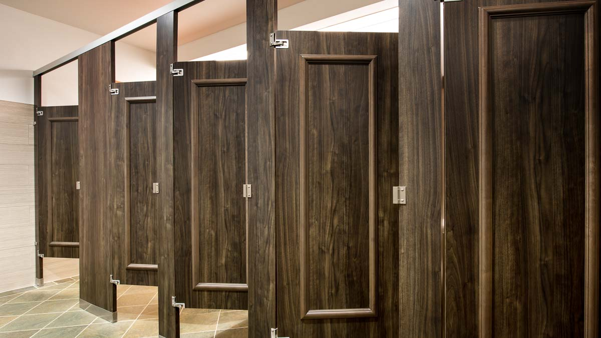 Green tone, wood grain plastic laminate standard size bathroom partitions featuring standard size doors with picture frame molding.