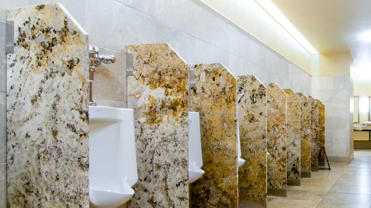 Nine brown, tan and white marbled look engineer stone urinal privacy screens in impressive, large men's casino bathroom.