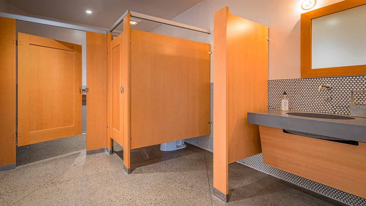 Men's bathroom shows two honey colored wood veneer partitions with captured panel doors and floor mount privacy urinal screen next to stone vanity.