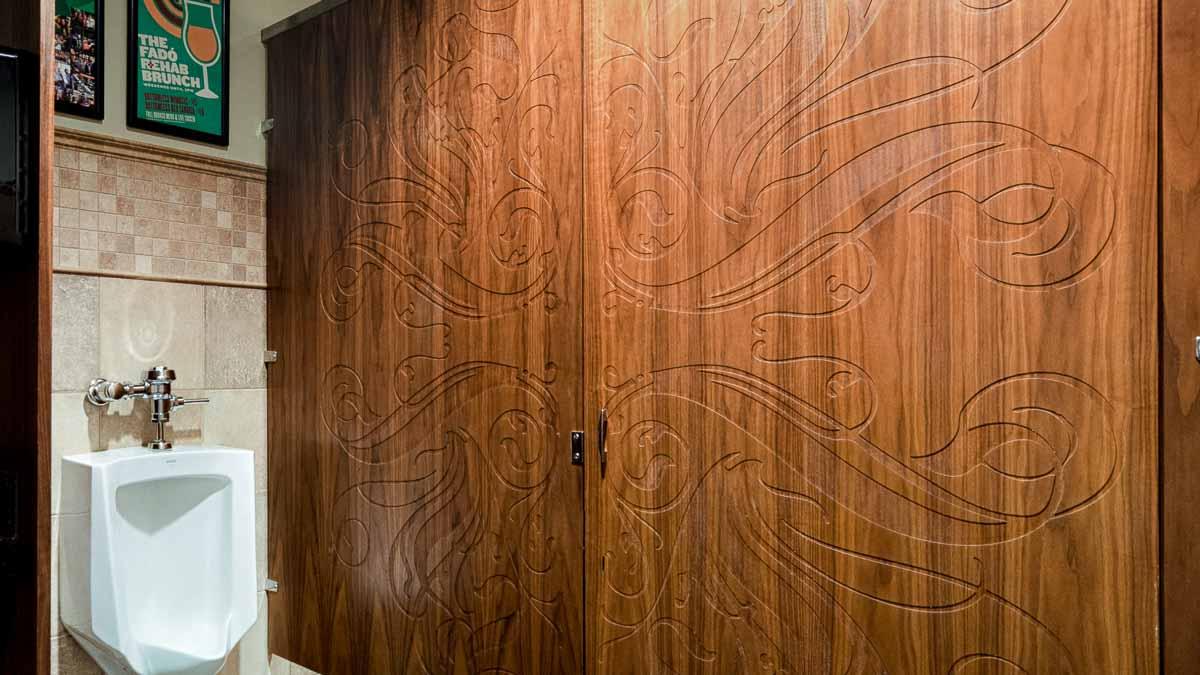 Intricate scroll medallion engraving on brown wood veneer door and panel in restaurant men's bathroom showcasing individual custom design.