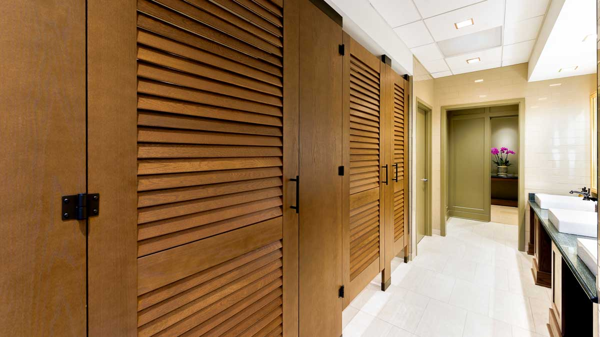 Upscale bathroom showing three, full height wood grain laminate partitions with louver doors opposite green marble vanity with white raised sinks.