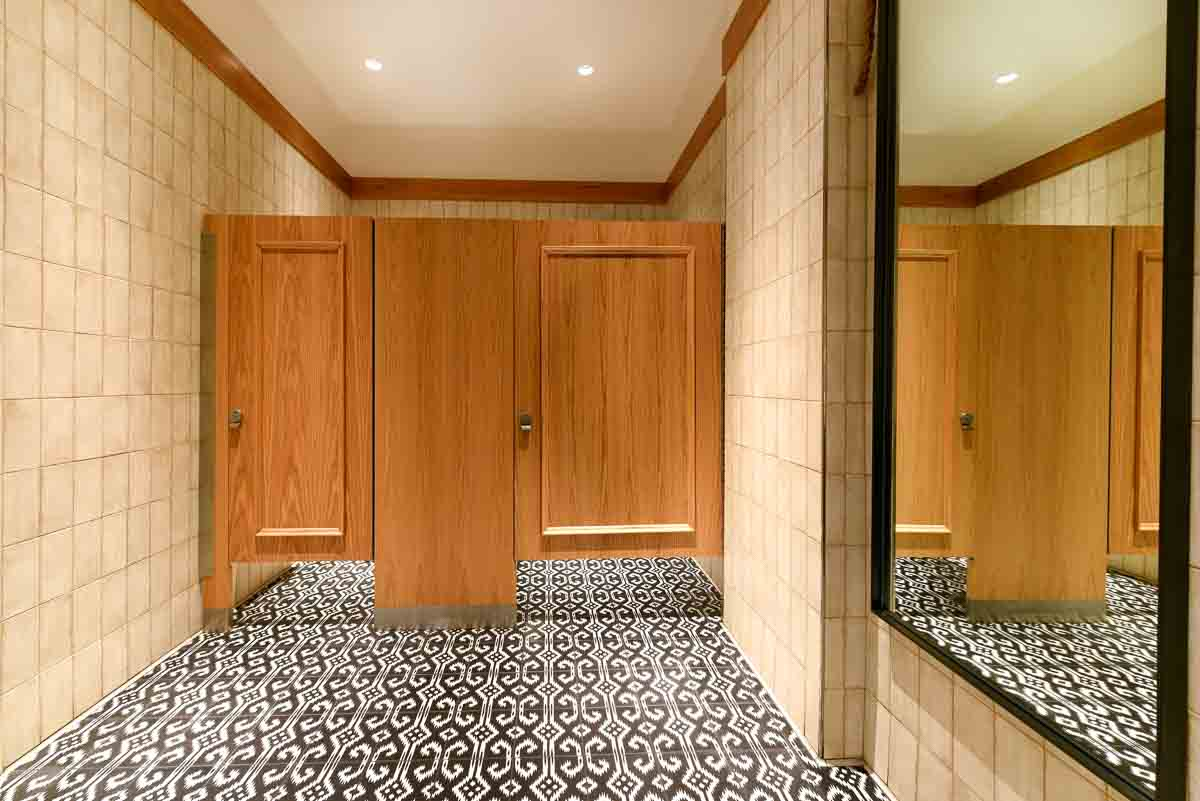 Two standard size floor mount partitions between tan tiled walls show wood veneer pilasters and molding on doors. Black and white geometric floor.