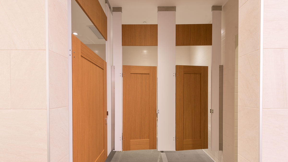 Large white tiled trendy business gym bathroom shows ceiling hung honey colored, wood grain captured panel doors with transoms and white pilasters.
