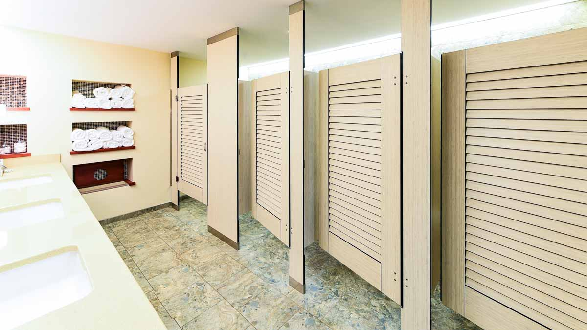Updated Country Club locker room features off-white, standard size compact laminate partitions and louver doors. Rolled towels on shelf.