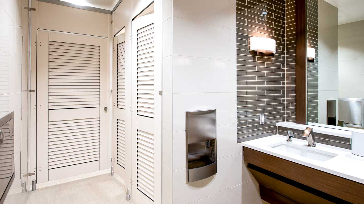 Urban dealership showroom bathroom shows high privacy European style toilet partition with white laminate louver doors and transoms. Brown tile room.