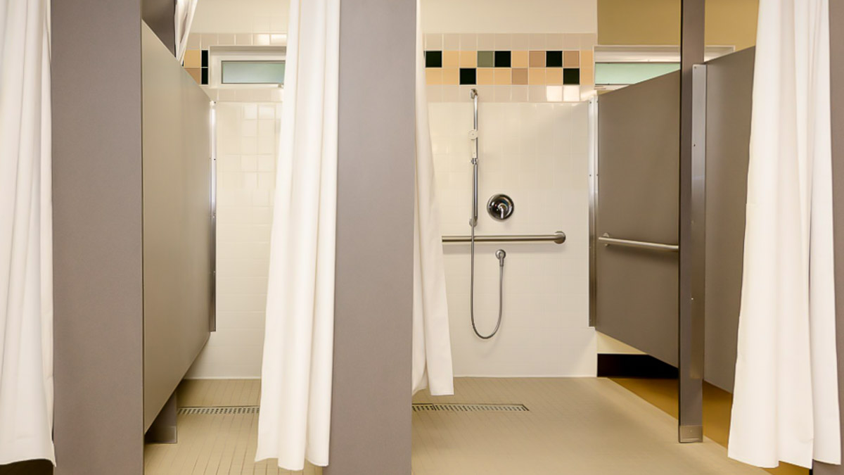 Open shower curtain shows inside of white tiled shower. Pilasters and panels are durable, compact laminate in headrail braced configuration.