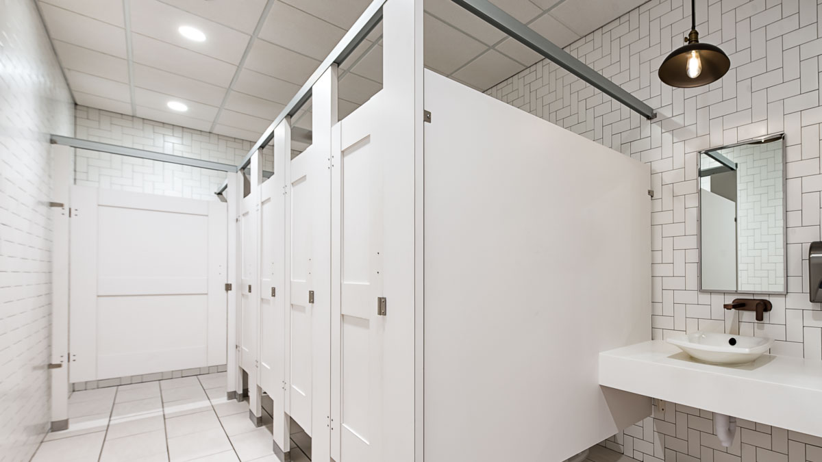 Bright, all-white bathroom showcasing five laminate, standard size partitions and captured panel doors with mid rail in headrail braced configuration.