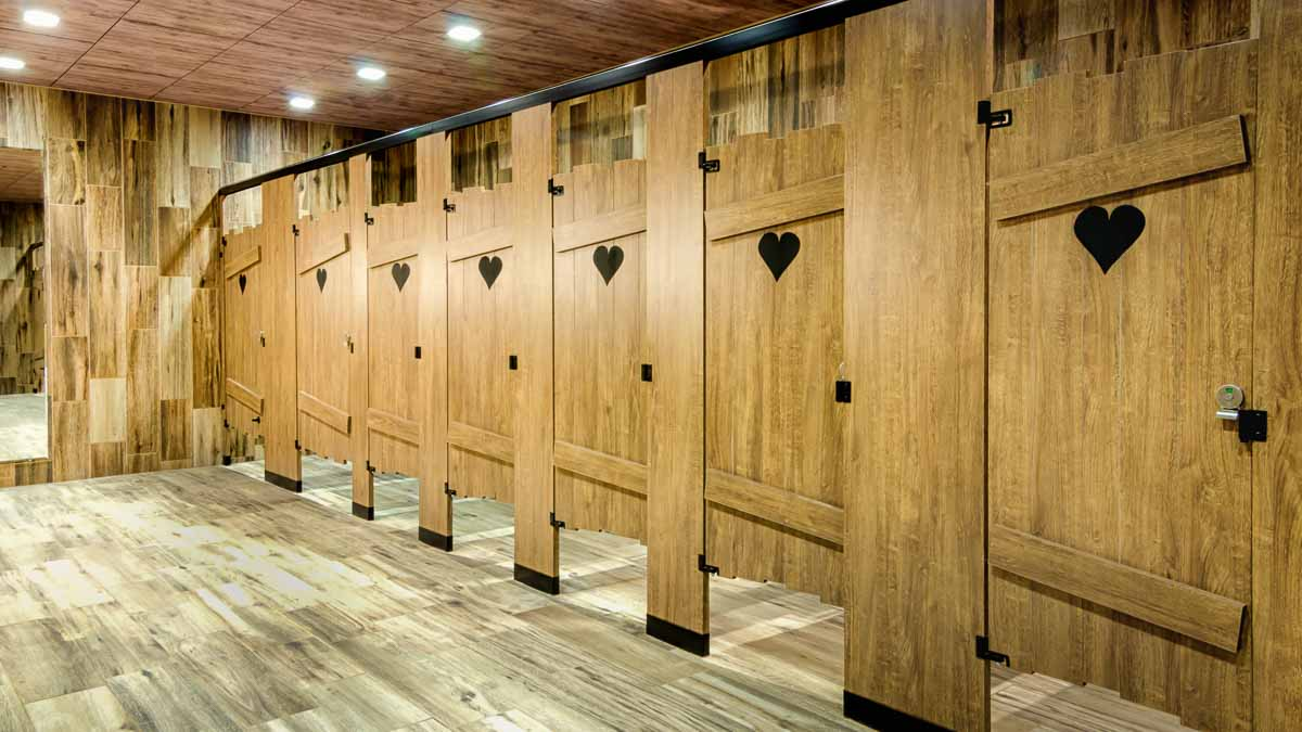 Custom shape bathroom partitions featuring heart shape engraving on brown, outhouse look laminate doors with purposeful uneven edges.