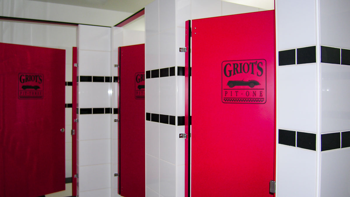 Bright red doors with black engraving of company name and logo compliment the white and black tiled public bathroom.