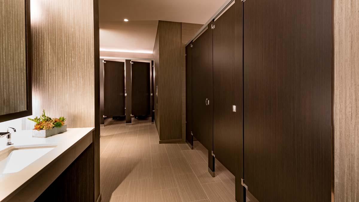 Spacious posh hotel bathroom has multiple, rich dark brown full height laminate partitions. Simplistic design creates open, fresh feel.