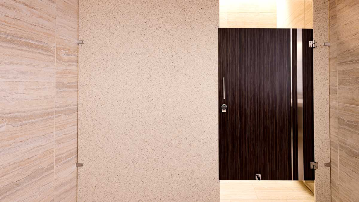 Variegated tan tiled wall and floor in luxurious bathroom with solid surface panel and a brown laminate door with vertical, stainless steel inserts.