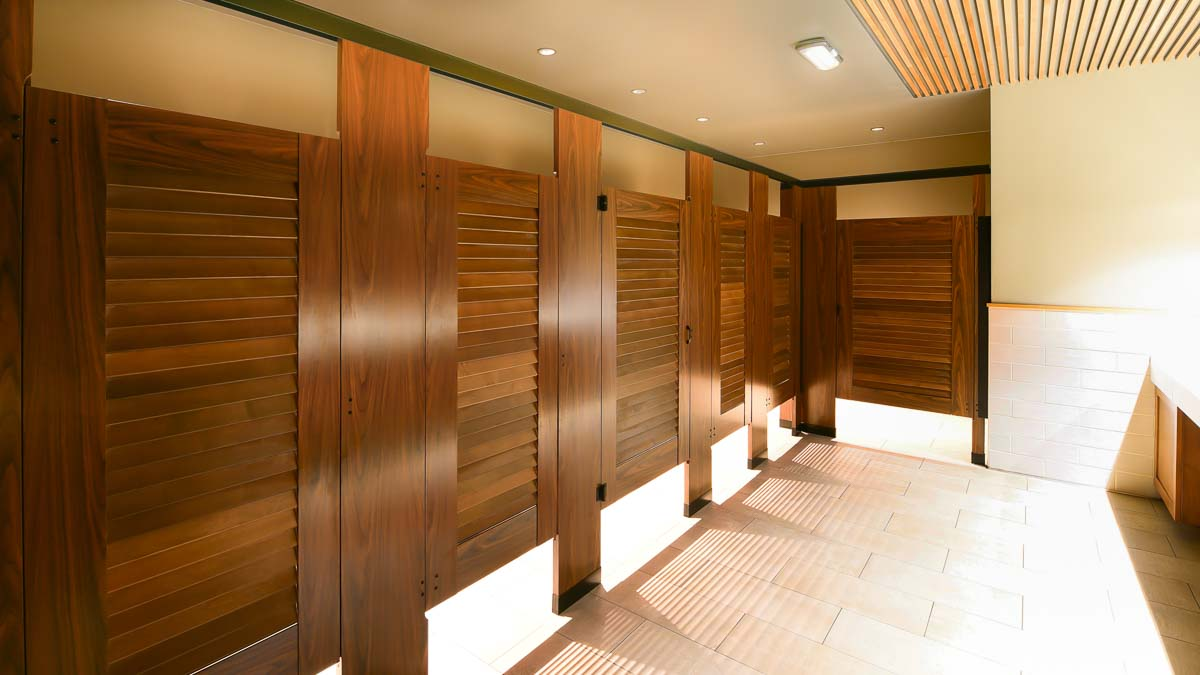 Stylish bathroom showing five zero sightline dark wood grain laminate partitions with louver doors in headrail braced configuration.