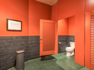 Winery bathroom painted bright orange in ceiling hung style with two louver doors and transom. Octagonal floor tile and wine glass print on wall.